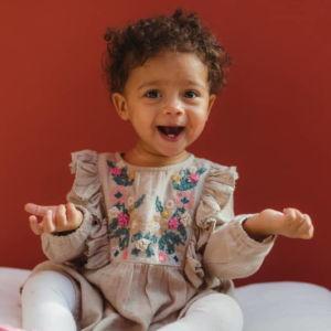 Musikgarten für Babys in Fürth - ein lachendes Mädchen mit dunkler Haut und süßen Locken