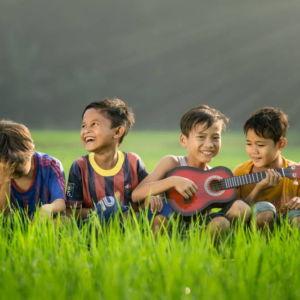 Musikkurse für Kinder in Fürth - vier Jungs auf einer Wiese mit einer Gitarre