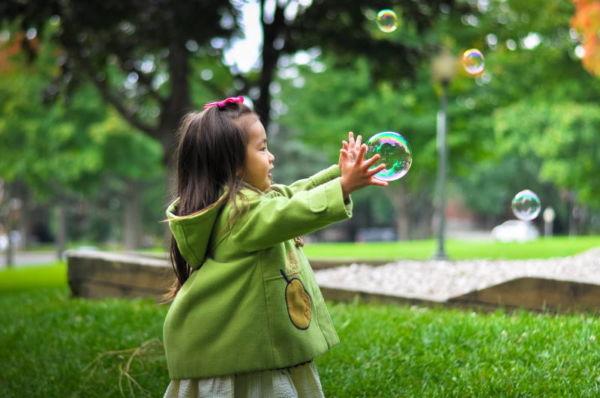 Musikgarten für Kleinkinder in Fürth - Mädchen versucht eine Seifenblase zu fangen