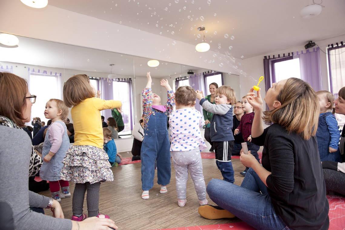 Musikgarten für Babys in Fürth - eine Mutter wirft ihr lachendes Kleinkind in die Luft